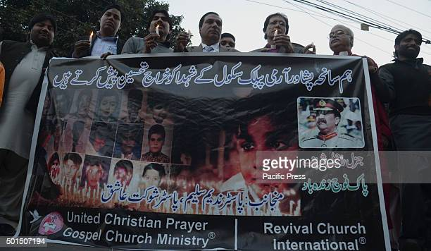 Pakistani workers of christian community Revival Church International hold candles during a vigil to pay tribute to the victims of the Peshawar...