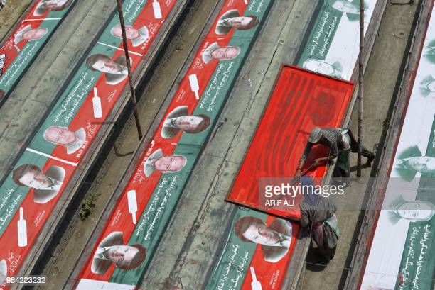 TOPSHOT Pakistani workers prepare election banners featuring images of Imran Khan cricketerturnedopposition leader and head of the Pakistan...