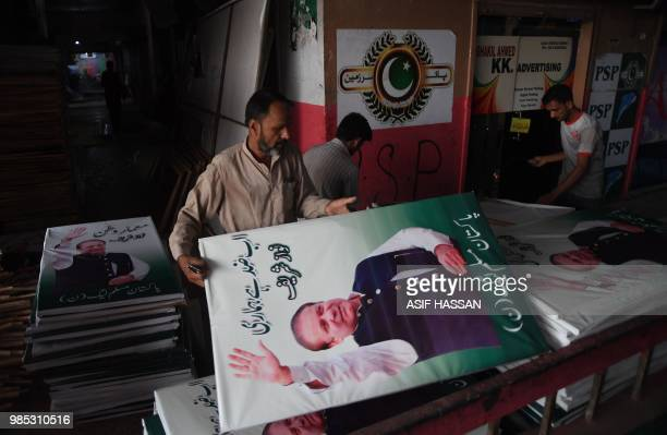 Pakistani workers prepare political parties posters for the upcoming general election at a market in Karachi on June 27, 2018. - Pakistan's...