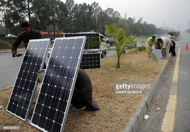 Pakistani workers prepare solar energy light panels on a road divider in Islamabad on February 2 2014 The country faces an electricity shortfall of...