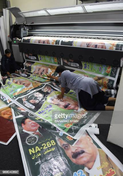 Pakistani workers print PML-N party posters at a printing shop ahead of the general election in Quetta on June 30, 2018. - Pakistan's forthcoming...