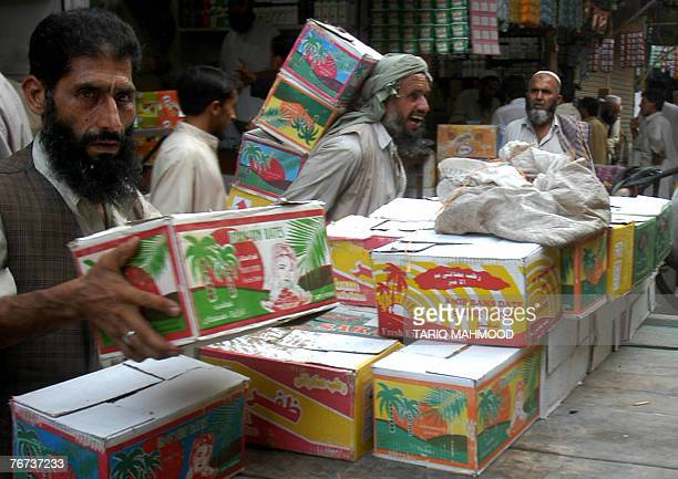 Pakistani workers unload boxes of dates at a market in Peshawar 12 September 2007 ahead of the start of the holy fasting month of Ramadan Ramadan...