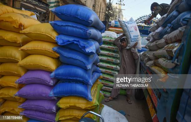 Pakistani workers unload rice sacks at a wholesale market in Karachi on April 8 2019 Pakistan will continue to face macroeconomic challenges despite...