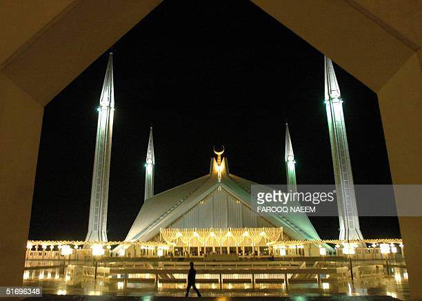 Pakistani worshipper walks in front of the illuminated Faisal Mosque in Islamabad 08 November 2004 Muslims are preparing to decorate the mosque for...