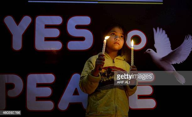 A Pakistani young girl holds lit candles for the victims of an attack by Taliban gunmen on an armyrun school in Peshawar in Lahore on December 17...