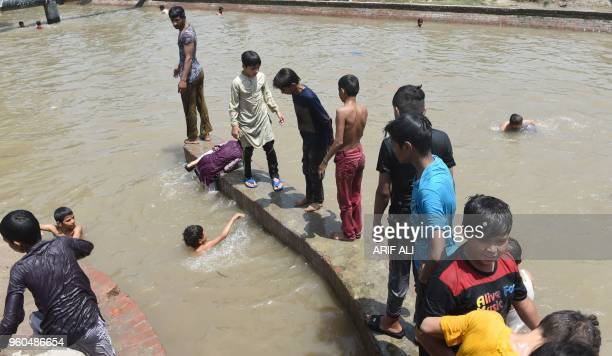Pakistani youth enjoy a swim in a canal during a hot summer day in Lahore on May 20 2018