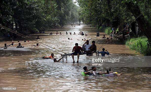 Pakistani youth enjoy swimming in a river canal on a hot day in Lahore on May 26 2013 Temperatures dropped by three to four degrees Celsius in many...