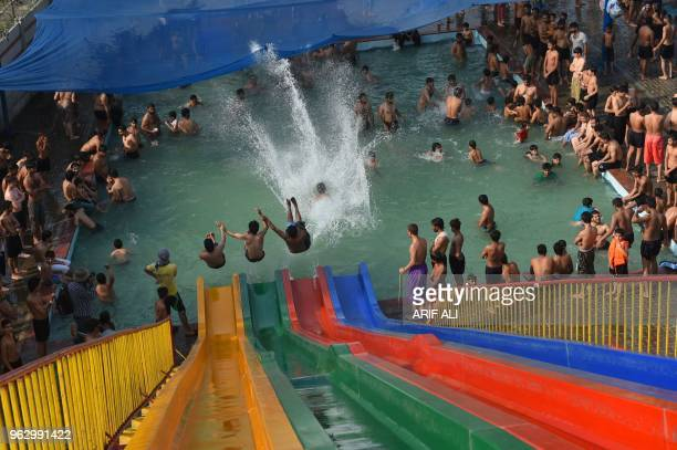 TOPSHOT Pakistani youth slide down a water slide during a a hot day in Lahore on May 27 2018