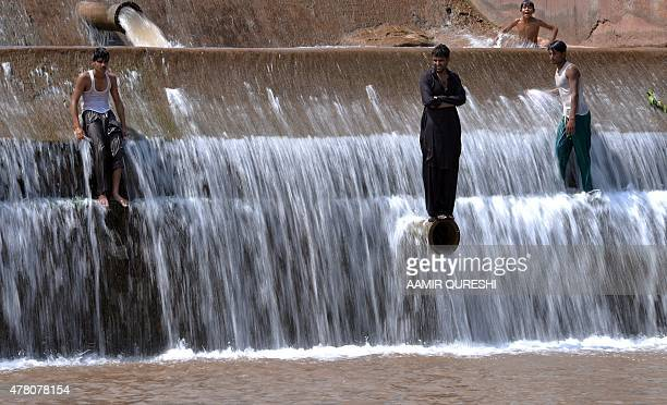 Pakistani youths cool themselves off at a river during a heatwave on the outskirts of Islamabad on June 22 2015 A heatwave in Pakistan's largest city...