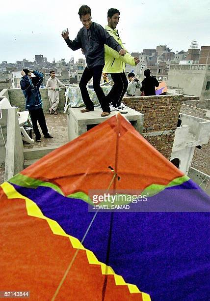 Pakistani youths dance as they celebrate Basant or kite flying festival in Lahore 06 February 2005 Thousands of people perched on roof tops in the...