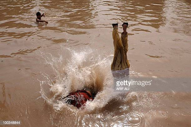 Pakistani youths jump into a canal to cool themselves in Lahore on May 23 2010 The highest maximum temperature of 50 Centigrade was recorded at Sibbi...