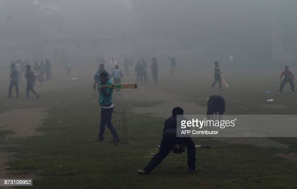 Pakistani youths play cricket amid heavy smog in Lahore on November 12 2017 Large swathes of Pakistan and north India see a spike in pollution at the...