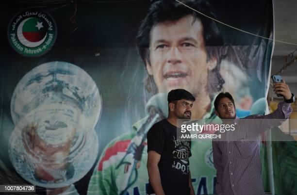 Pakistani youths take a selfie with a poster of World Cup cricket hero turned politician and head of the Pakistan Tehreek-e-Insaf party Imran Khan,...