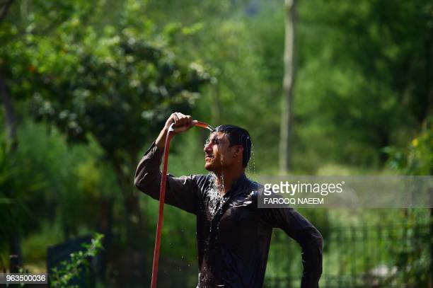 Pakistani zoo employee showers himself with water from a hose on a hot summer day in Islamabad on May 29, 2018.