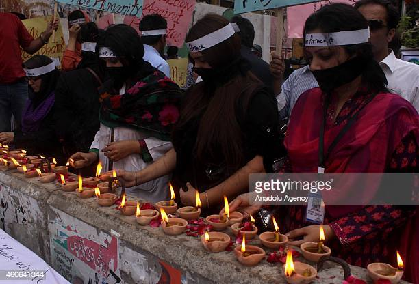 Pakistanis covering their mouths hold candle light vigil in Karachi Pakistan on December 18 in memory of the victims of the Taliban assault on an...