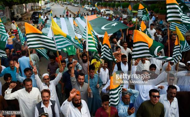 Pakistanis demonstrators carry flags of Pakistanadministered Kashmir during an antiIndian protest in Karachi on August 18 2019 Tensions have soared...