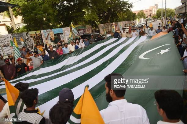 Pakistanis demonstrators hold a giant flag of Pakistanadministered Kashmir during an antiIndian protest in Karachi on August 18 2019 Tensions have...