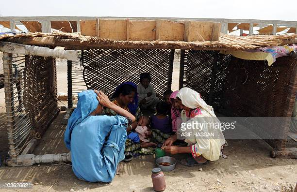 Pakistanis displaced by floods eat food in a temporary shelter made with charpois normally used as bed bases near a makeshift camp in Hyderabad on...