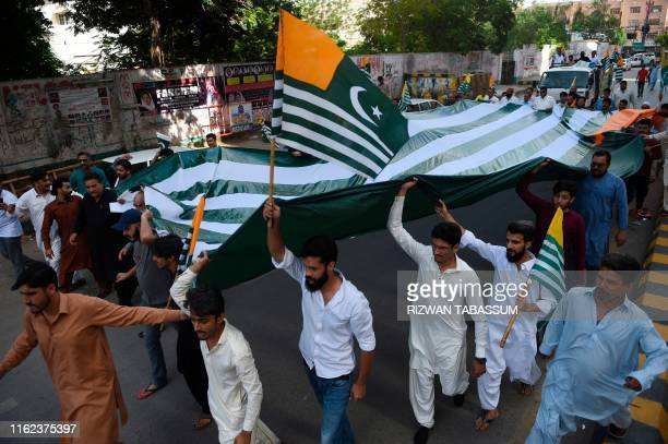 Pakistanis hold a giant flag of Pakistanadministered Kashmir during an antiIndian protest in Karachi on August 18 2019 Tensions have soared since...