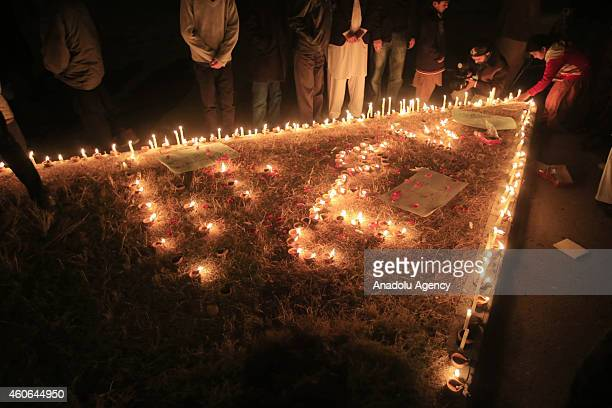 Pakistanis hold candle light vigil in front of the press club in Islamabad Pakistan on December 18 in memory of the victims of the Taliban assault on...