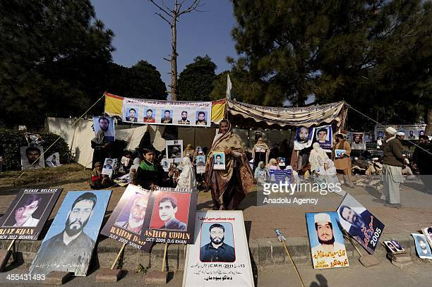 Pakistanis hold pictures of their relatives during a sitin protest in a camp set up by families of missing people at D Square outside the parliament...