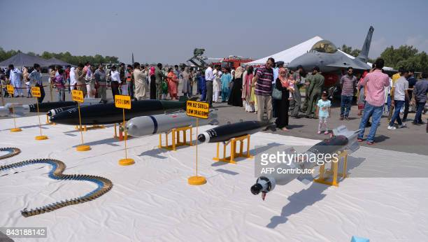Pakistanis look at missiles and a jet fighter during celebrations to mark Defence Day at the Nur Khan military airbase in Islamabad on September 6...