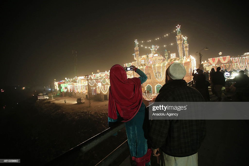 Pakistanis take pictures of the buildings as streets and buildings are decorated with lights and ornaments within the ceremony marking the 1444th anniversary of the birthday of Prophet Mohammad, Mawlid al Nabi, in Rawalpindi, Pakistan on January 3, 2015.