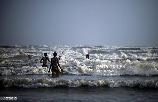 Pakistanis wade in waters off the coast of Clifton beach on the Arabian Sea in Karachi on June 8 2011 Pakistan Meteorological Department warned that...