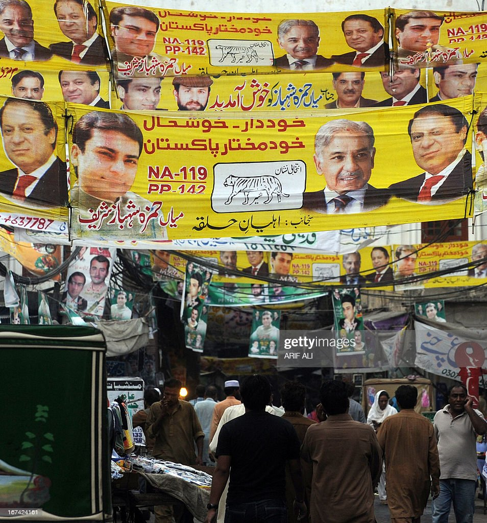 Pakistanis walk under electoral banners on a street in Lahore on April 25, 2013. Amnesty International called on Pakistan to investigate a wave of attacks and threats against politicians and election workers that have marred the run-up to key polls next month.