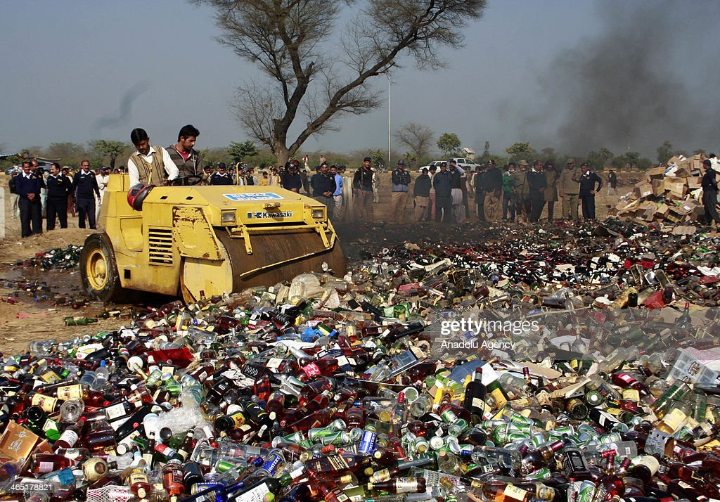 Pakistanis watch as customs officials use a steamroller to crush bottles of liquor at a ceremony on the International Customs Day in the outskirts of Lahore, on January 26, 2014.