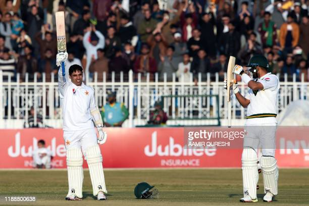 Pakistan's Abid Ali celebrates after scoring century as teammate Pakistan's Babar Azam applauds during the fifth and final day of the first Test...