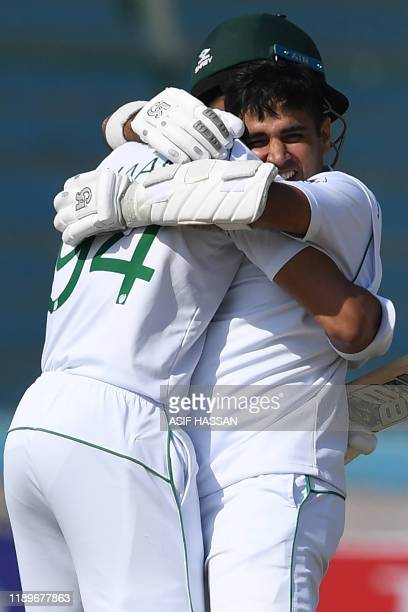 Pakistan's Abid Ali celebrates with teammate Shan Masood after scoring a century during the third day of the second Test cricket match between...