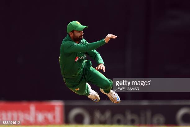 TOPSHOT Pakistan's Ahmed Shehzad leaps in the air as he fields a ball during the third of fourT20Imatch between West Indies and Pakistan at the...
