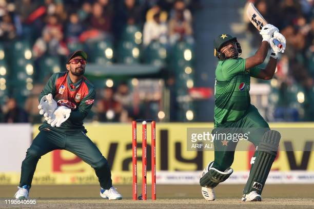 Pakistan's Ahsan Ali plays a shot as Bangladesh's wicketkeeper Liton Das looks on during the first T20 international cricket match of a threematch...