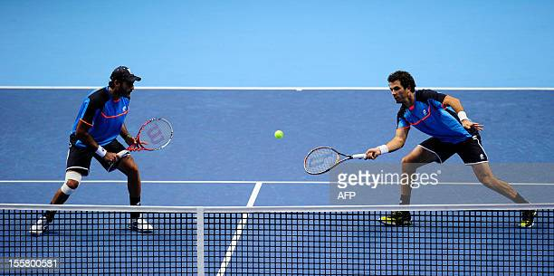Pakistan's AisamUlHaq Qureshi stands by as Netherlands' JeanJulien Rojer reaches for a return against US tennis player Bob Bryan and his partner US...