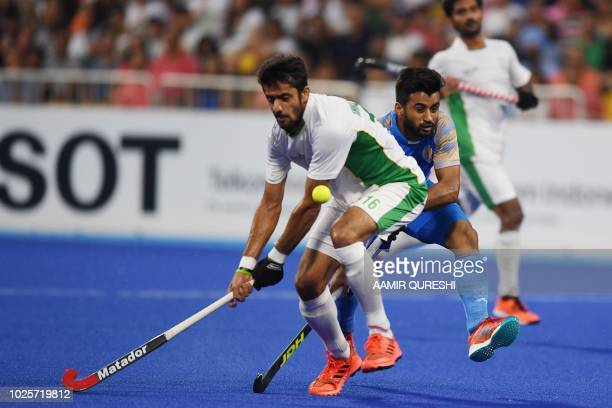 Pakistan's Ammad Shakeel Butt and India's Manpreet Singh fight for the ball during the men's field hockey bronze medal match between India and...