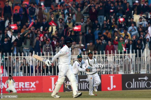 Pakistan's Asad Shafiq and Mohammad Rizwan celebrate the dismissal of Sri Lanka's Angelo Mathews during the first day of the first Test cricket match...