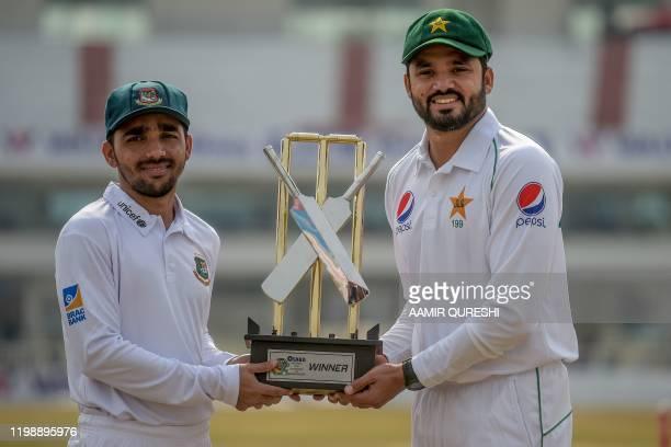 Pakistan's Azhar Ali and his Bangladesh counterpart Mominul Haque hold the Test series trophy at the Rawalpindi Cricket Stadium in Rawalpindi on...