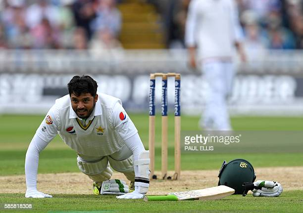 Pakistan's Azhar Ali celebrates by doing pressups after reaching his century during play on the second day of the third test cricket match between...
