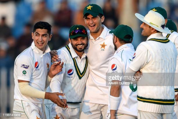 Pakistan's Azhar Ali celebrates with teammates Naseem Shah and Shaheen Shah Afridi after the dismissal of Bangladesh's Mohammad Mithun during the...