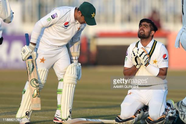 Pakistan's Babar Azam celebrates after scoring century as teammate Pakistan's Abid Ali looks on during the fifth and final day of the first Test...