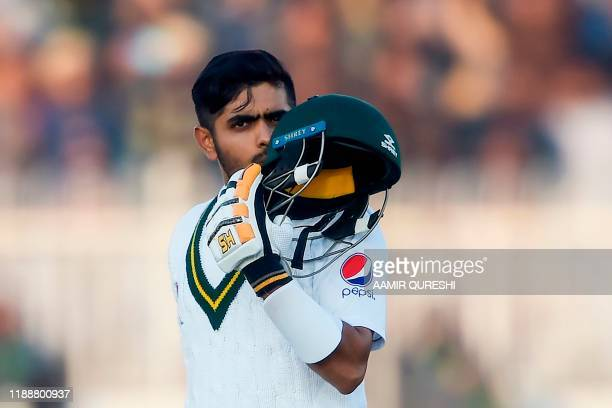 Pakistan's Babar Azam kisses his helmet after scoring century during the fifth and final day of the first Test cricket match between Pakistan and Sri...