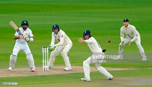 Pakistan's Babar Azam plays a shot as England's Jos Buttler , Ollie Pope and Ben Stokes look on during the first day of the first Test cricket match...
