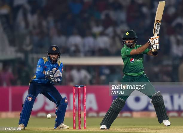 Pakistan's Babar Azam plays a shot as Sri Lanka's Sadeera Samarawickrama looks on during the third and final Twenty20 International cricket match...