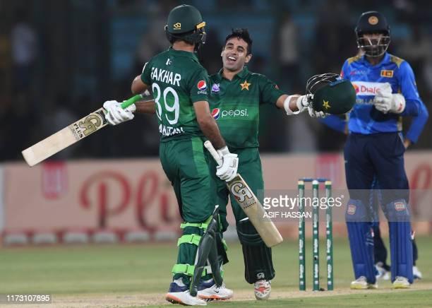 Pakistan's batsman Abid Ali celebrates with teammate Fakhar Zaman after scoring 50 runs as Sri Lanka's wicketkeeper Minod Bhanuka looks on during the...