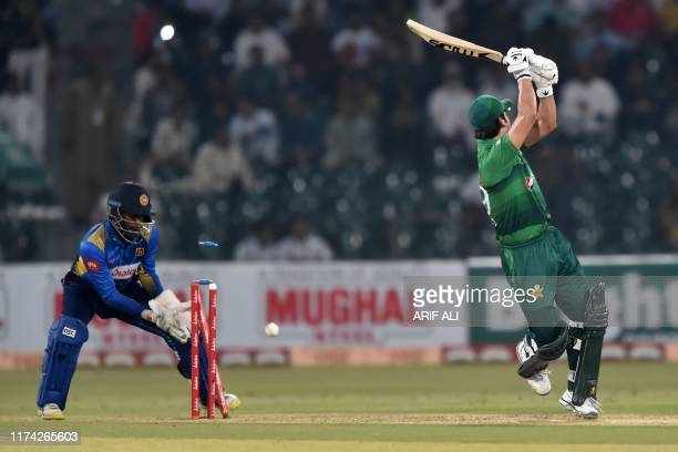 Pakistan's batsman Ahmed Shehzad is bowled out Sri Lanka's wicketkeeper Minod Bhanuka looks on during the second Twenty20 International cricket match...