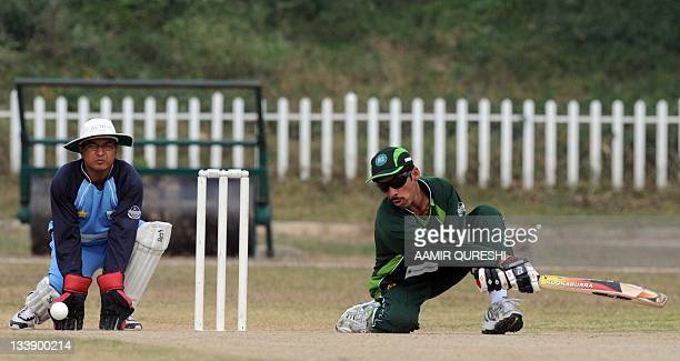 Pakistan's blind cricketer Mohammad Zafar plays a shot as Indian wicketkeeper Manvendra takes position during the first oneday international match...