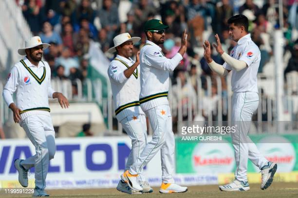 Pakistan's bowler Naseem Shah celebrates with teammates after taking the dismissal of Bangladesh's Saif Hassan during the third day of the first...