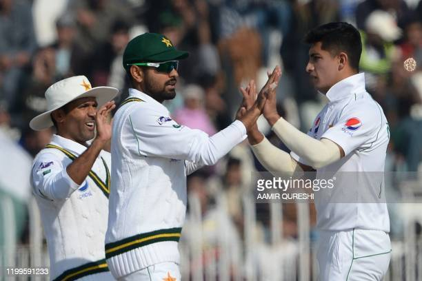Pakistan's bowler Naseem Shah celebrates with teammates Babar Azam and Asad Shafiq after the dismissal of Bangladesh's Saif Hassan during the third...