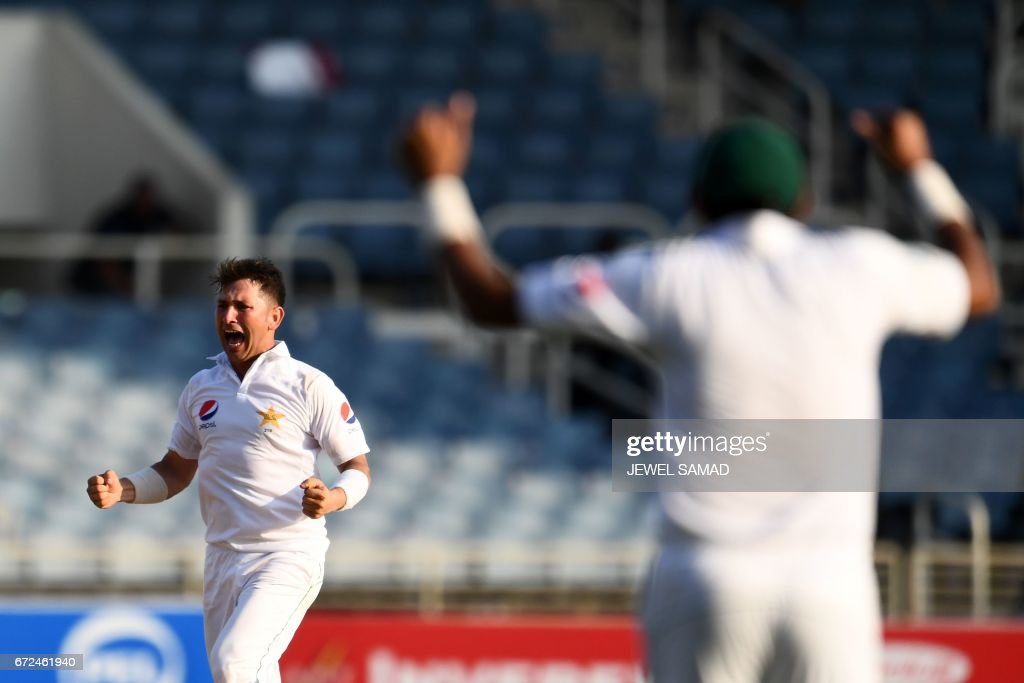 Pakistan's bowler Yasir Shah(L) celebrates after dismissing West Indies' batsman Shai Hope on day four of the first Test match between West Indies and Pakistan at the Sabina Park in Kingston, Jamaica, on April 24, 2017. / AFP PHOTO / Jewel SAMAD